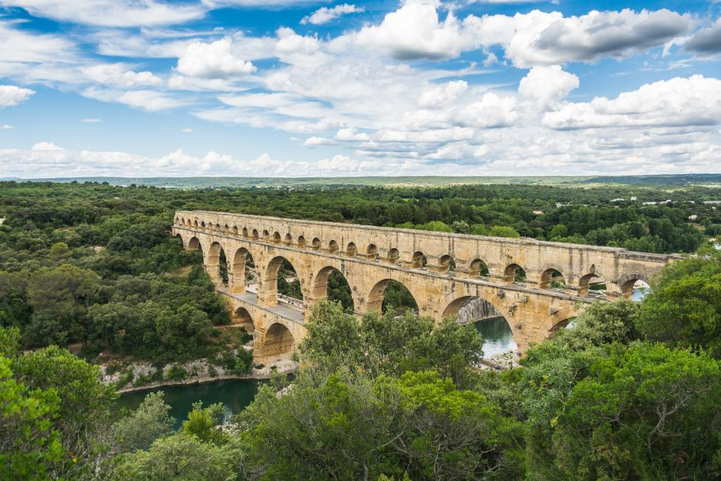 Fig.2: A Roman Bridge in Gard, France. Roman engineering required already some attributes of modern work design, with the division of labour and specialisation. Photo by Z S on Unsplash